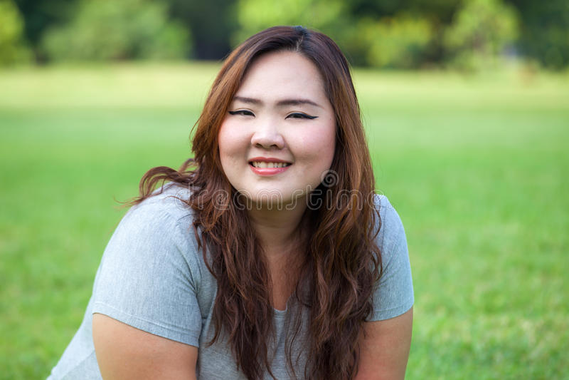Glückliche fetthaltige asiatische Frauenaufstellung im Freien stockfotografie