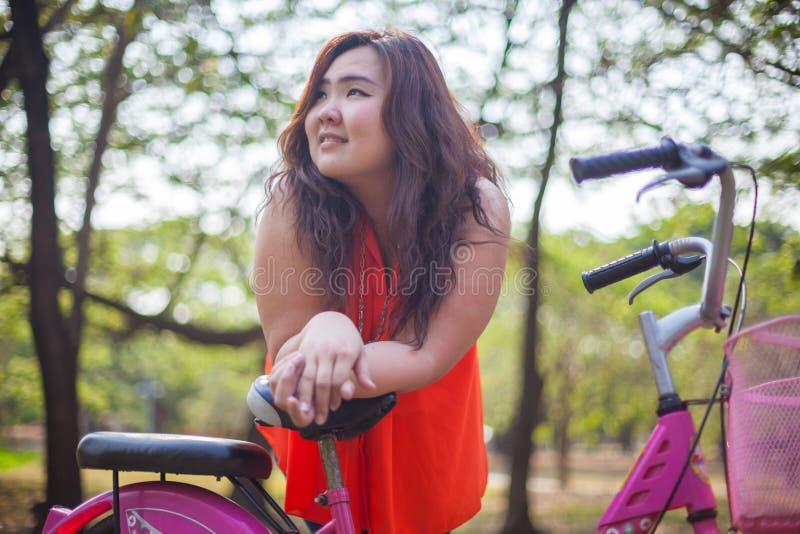 Glückliche fetthaltige Frau, die mit Fahrrad aufwirft lizenzfreies stockfoto