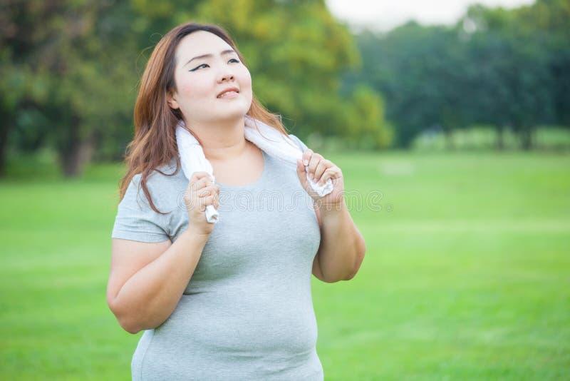Glückliche fetthaltige Sitzfrauenaufstellung im Freien lizenzfreies stockfoto