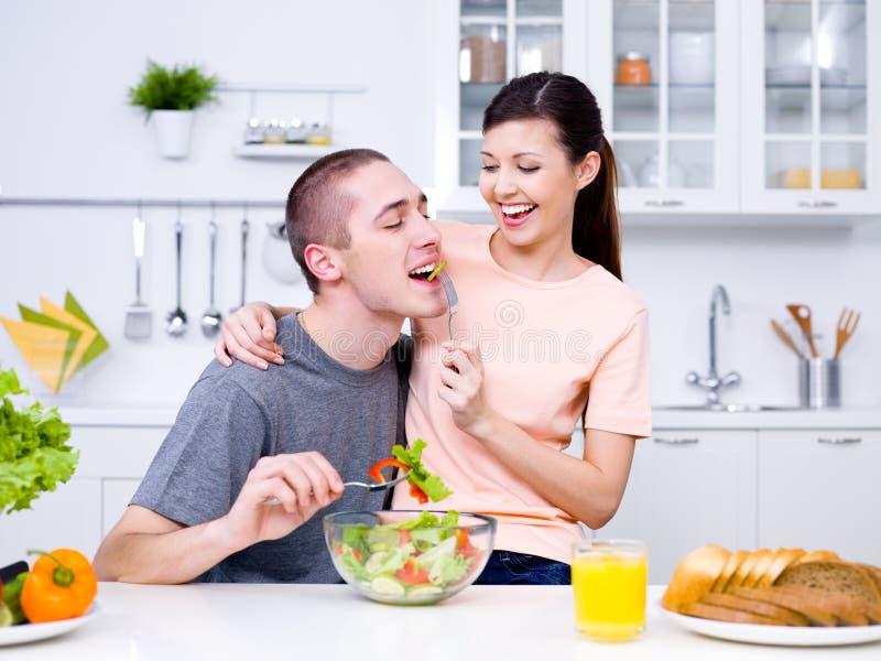 Glückliche flirtenpaare in der Küche lizenzfreies stockfoto