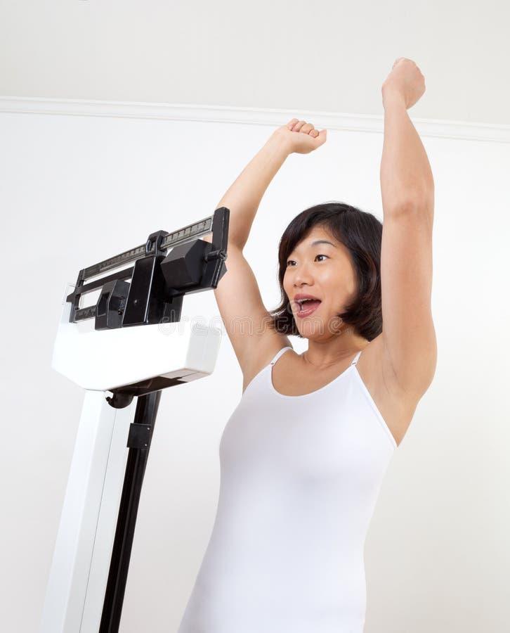 Glückliche Frau auf dem Gewicht-Skala-Zujubeln stockfotos