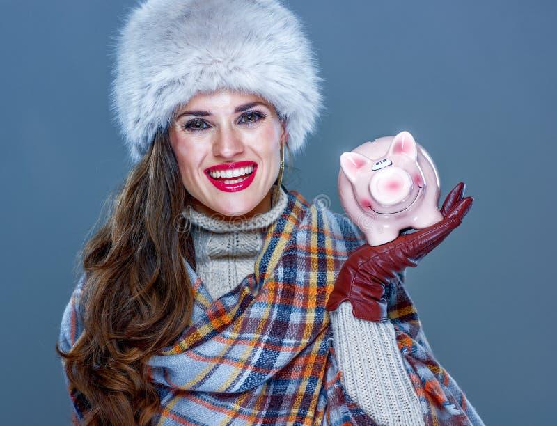 Glückliche Frau auf dem kalten blauen Hintergrund, der Sparschwein zeigt lizenzfreies stockbild