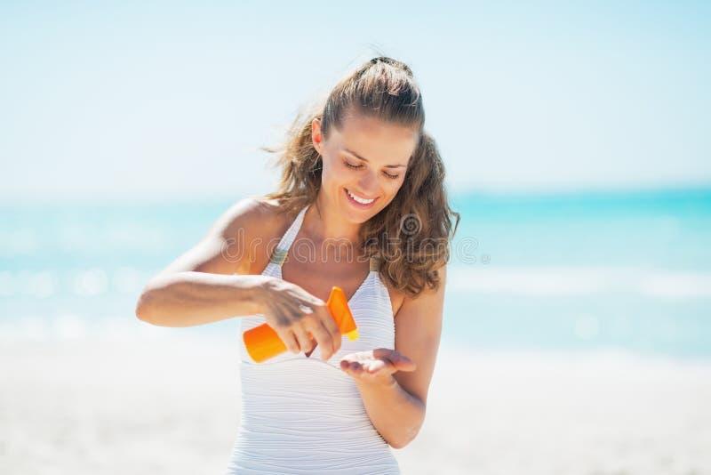 Glückliche Frau auf dem Strand, der Sonnenschutzcreme anwendet lizenzfreie stockbilder