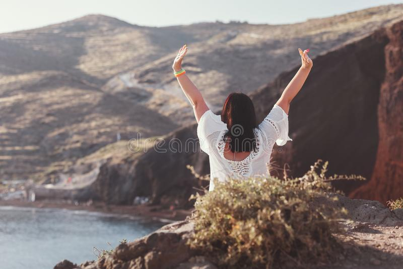 Glückliche Frau auf dem Strand mit den Händen oben, sitzend auf Felsen des berühmten roten Strandes, Santorini, Akrotiri, Grieche stockfotos