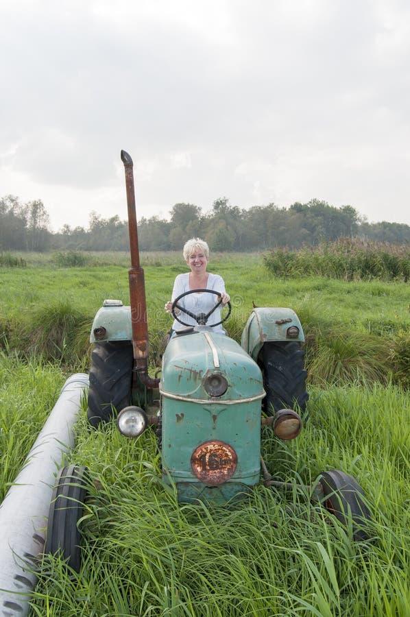 Glückliche Frau auf einem Traktor lizenzfreies stockfoto