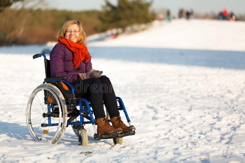 Glückliche Frau auf Rollstuhl im Schnee lizenzfreies stockbild