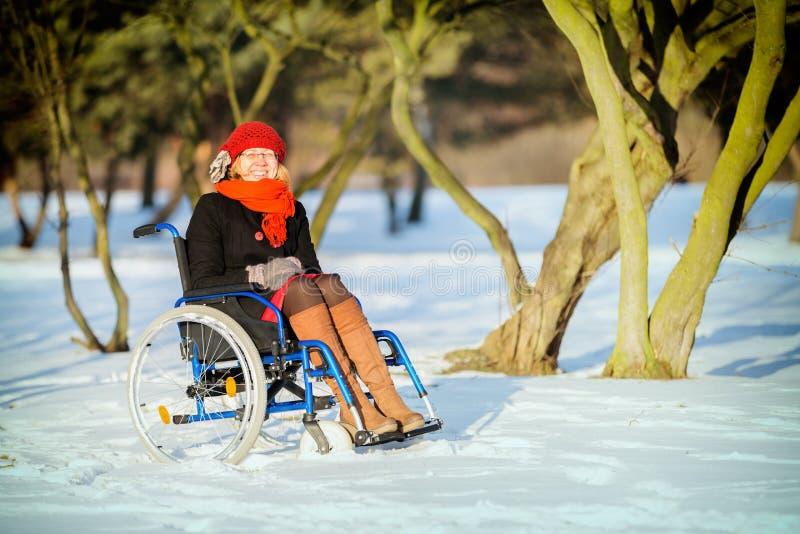 Glückliche Frau auf Rollstuhl im Schnee stockbild
