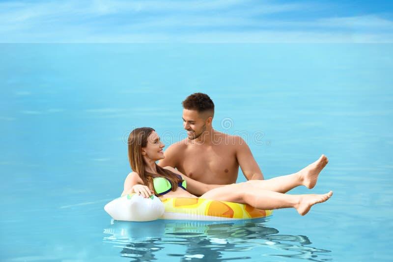 Glückliche Frau in Bikini, die auf aufblasbarem Ring treibt, und ihr Freund auf See lizenzfreies stockfoto