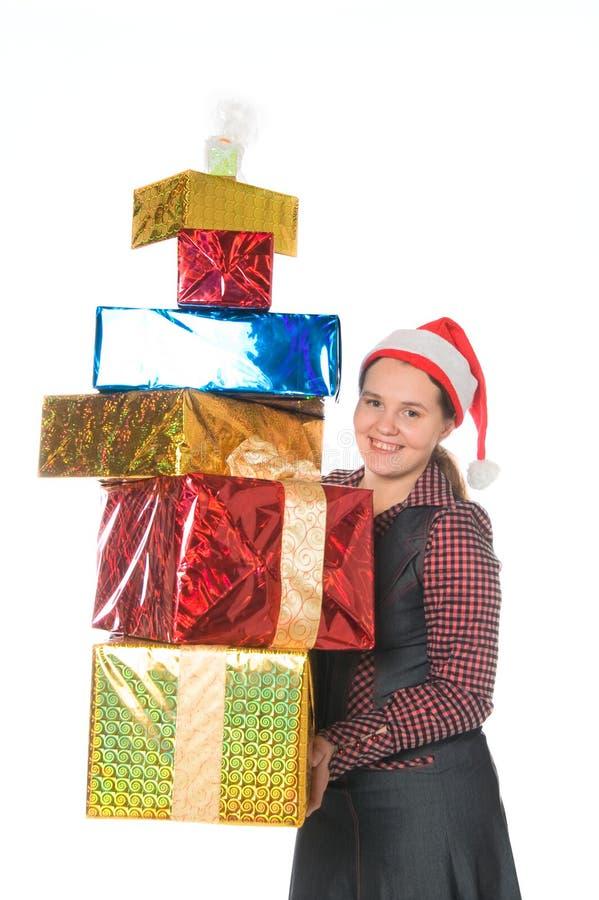 Glückliche Frau in der roten Schutzkappe mit Geschenken stockfotos