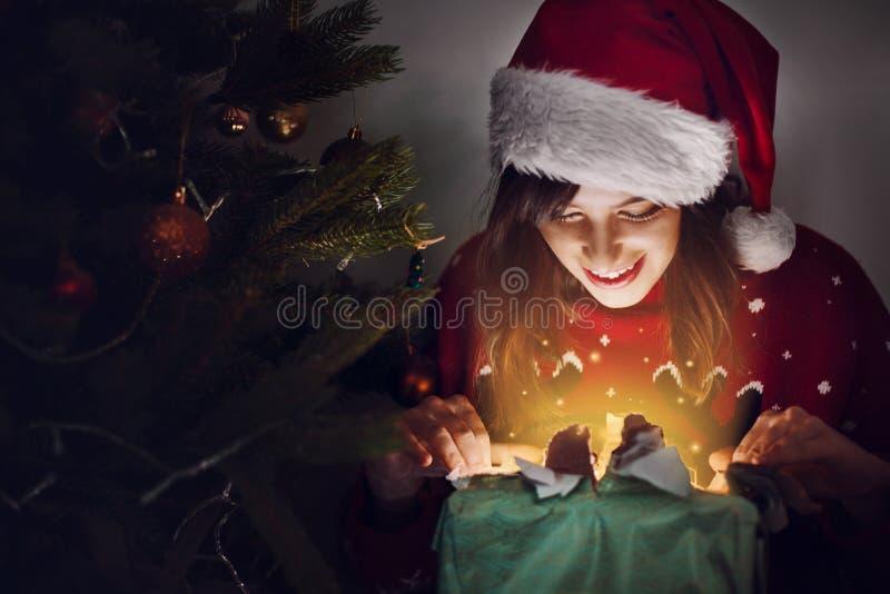 Glückliche Frau in der Sankt-Hutöffnungsgeschenkbox an Weihnachtsbaum ligh stockbild