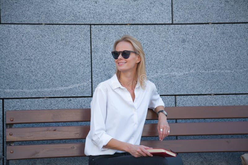 Glückliche Frau in der Sonnenbrille, die mit Buch sitzt lizenzfreie stockfotografie