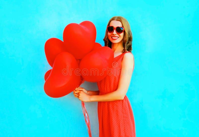 Glückliche Frau des Porträts mit Rot Ballone einer Luft auf Blau lizenzfreies stockfoto