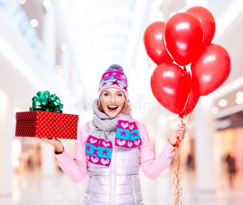 Glückliche Frau des Spaßes mit roter Geschenkbox und Ballonen am Geschäft stockfoto