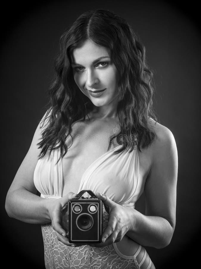 Glückliche Frau in Dessous mit Retrokamera stockfotografie