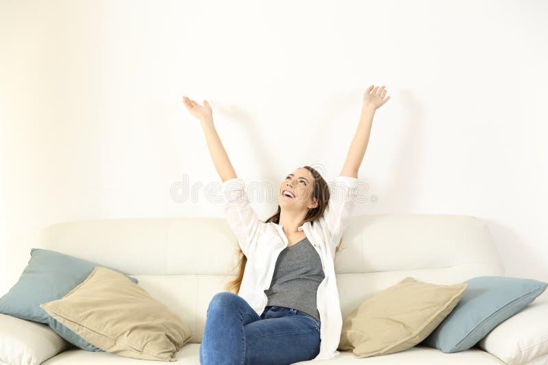 Glückliche Frau, die Arme anhebt und oben auf einer Couch schaut lizenzfreies stockfoto