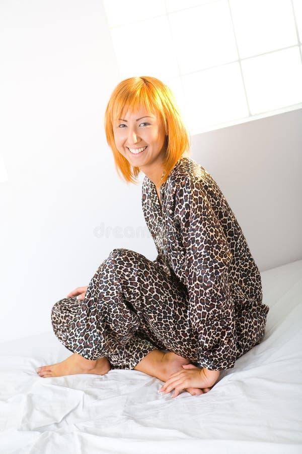 Glückliche Frau, die auf Bett sitzt stockfoto