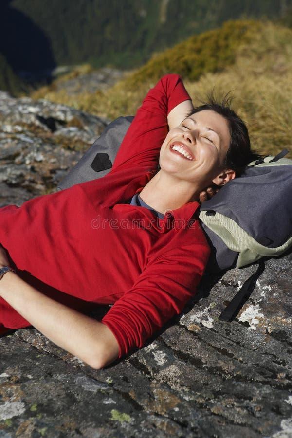 Glückliche Frau, die auf Boulder mit Rucksack liegt lizenzfreies stockbild