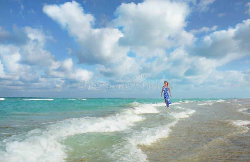 Glückliche Frau, die auf dem Strand geht und sich entspannt stockfoto