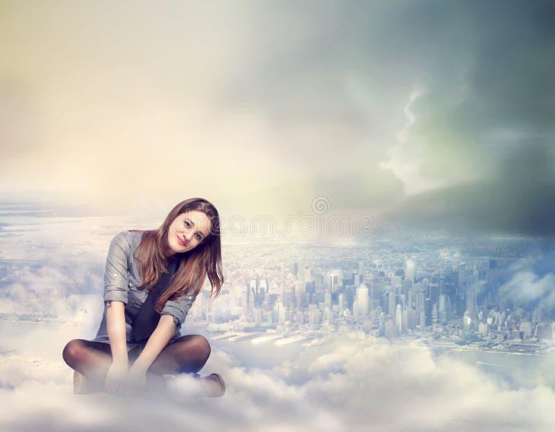 Glückliche Frau, die auf den Wolken sitzt stockbilder