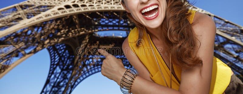 Glückliche Frau, die auf Eiffelturm in Paris, Frankreich zeigt stockfotografie