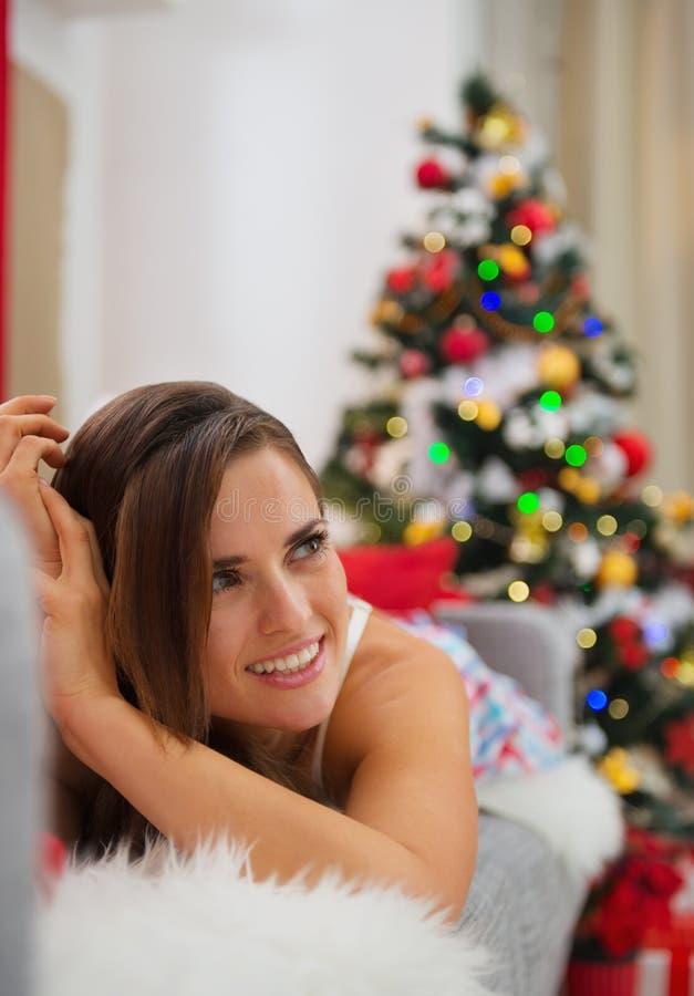 Download Glückliche Frau, Die Auf Sofa Nahe Weihnachtsbaum Legt Stockbild - Bild von kaukasisch, lebensstil: 27728231