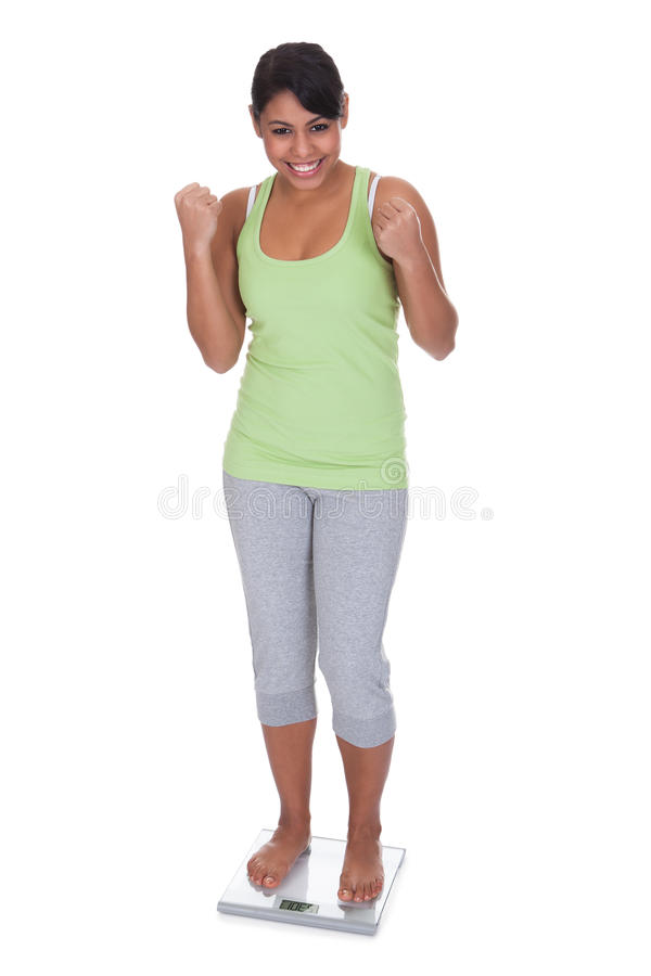 Glückliche Frau, die auf wiegender Skala steht stockfotos