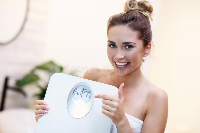 Glückliche Frau, die Badezimmerwaagen im Badezimmer hält lizenzfreies stockbild