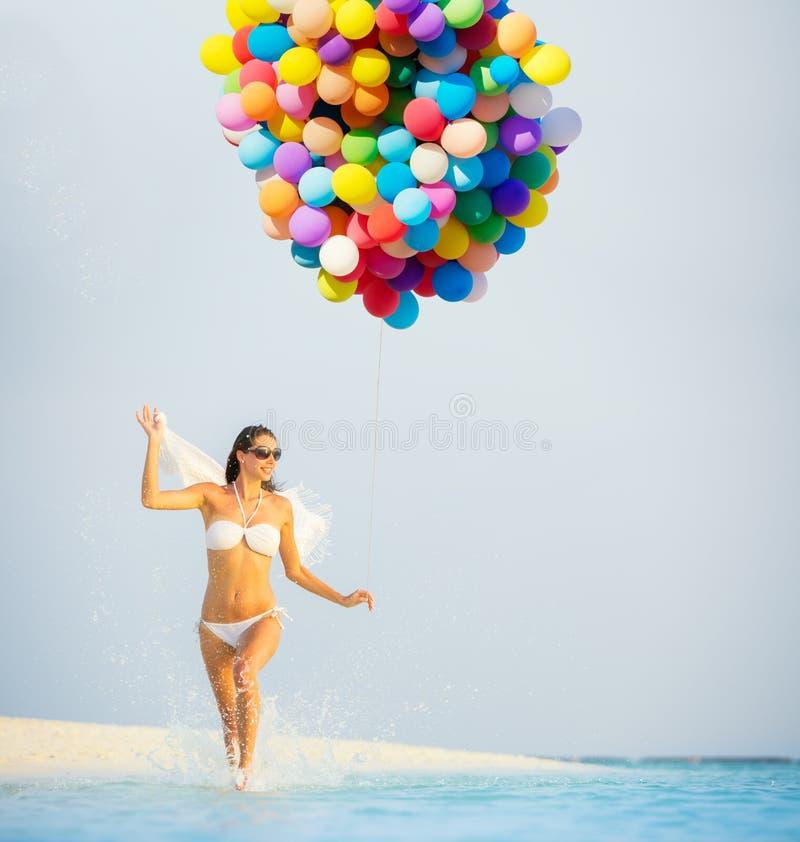 Glückliche Frau, die Ballone und Koffer auf Strand hält stockfoto