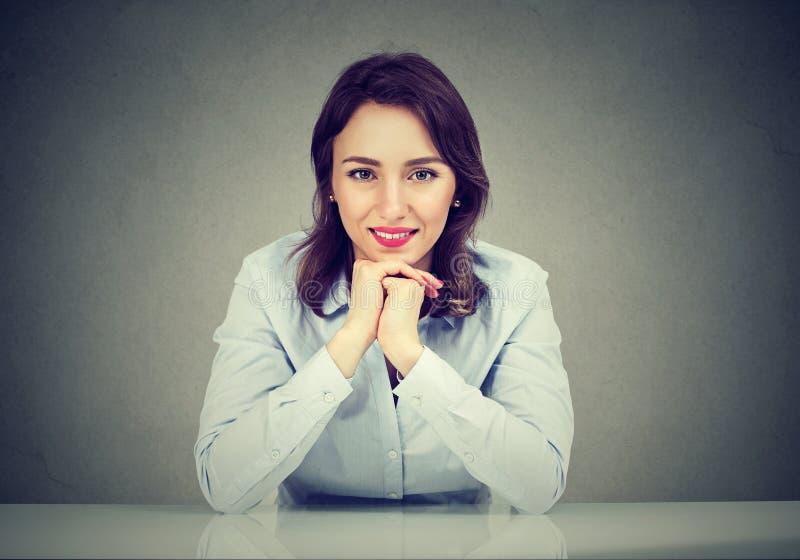 Glückliche Frau, die bei Tisch das Lächeln an der Kamera lehnt lizenzfreies stockfoto