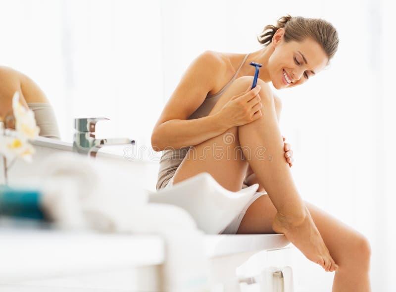 Glückliche Frau, die Beine nachdem dem Rasieren überprüft lizenzfreies stockfoto