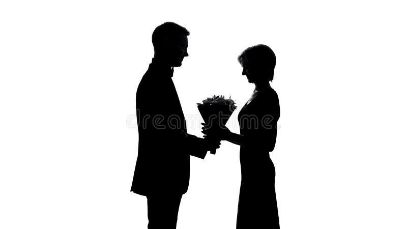 Glückliche Frau, die Blumenblumenstrauß vom Mann, romantisches Geschenk für Jahrestag empfängt lizenzfreies stockfoto