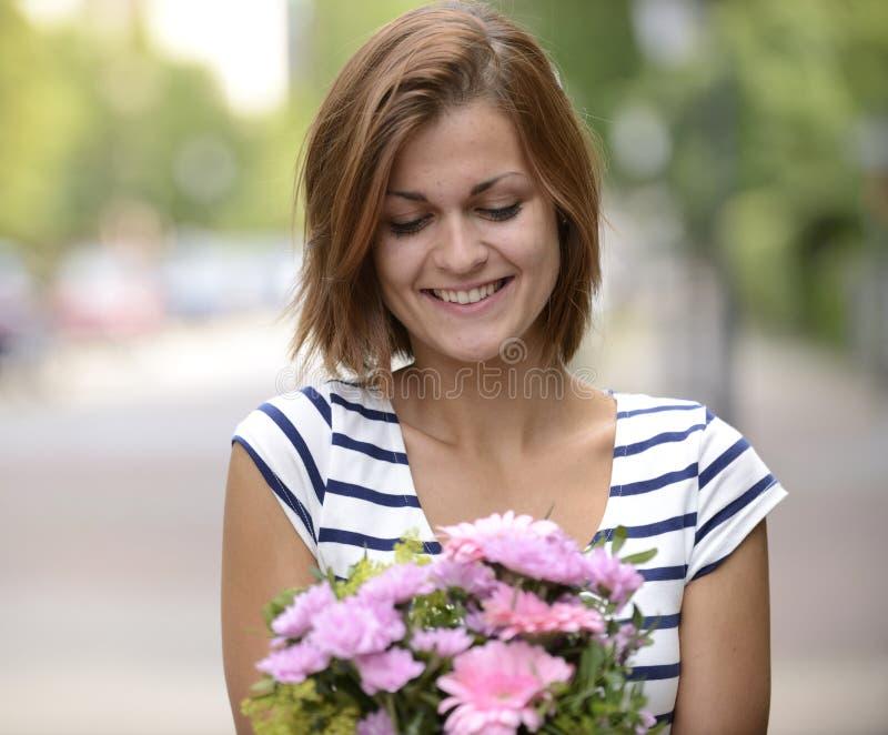 Glückliche Frau, die Blumengesteck hält stockfotos