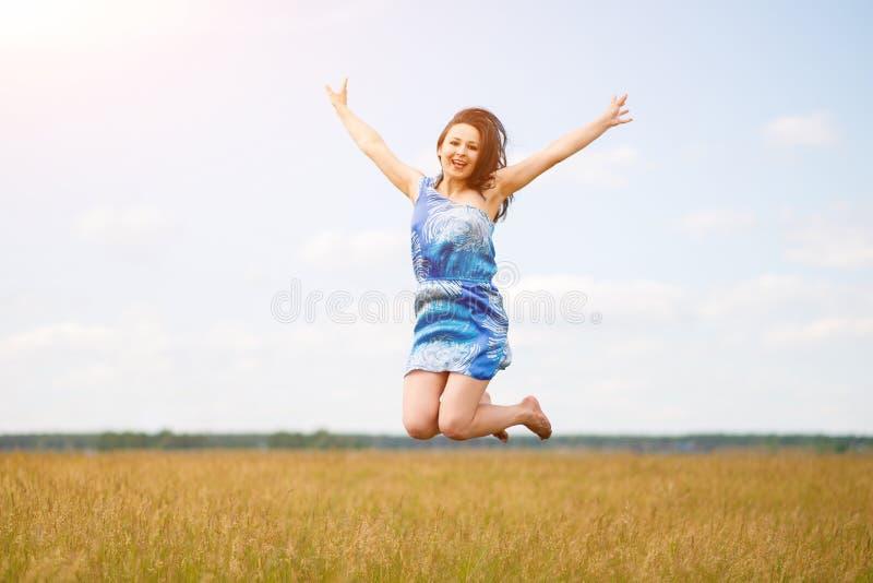 Glückliche Frau, die das Leben auf dem Gebiet am Tageslicht springt und genießt lizenzfreie stockfotos