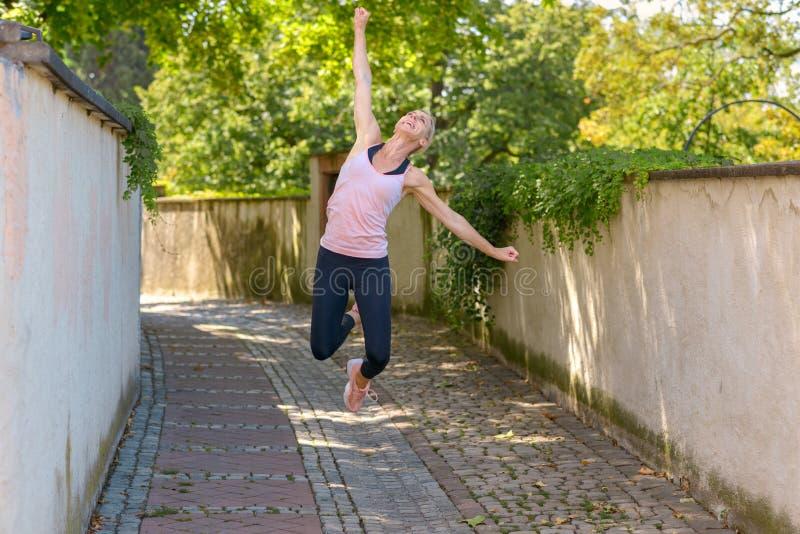 Glückliche Frau, die das Springen in die Luft feiert stockfotografie