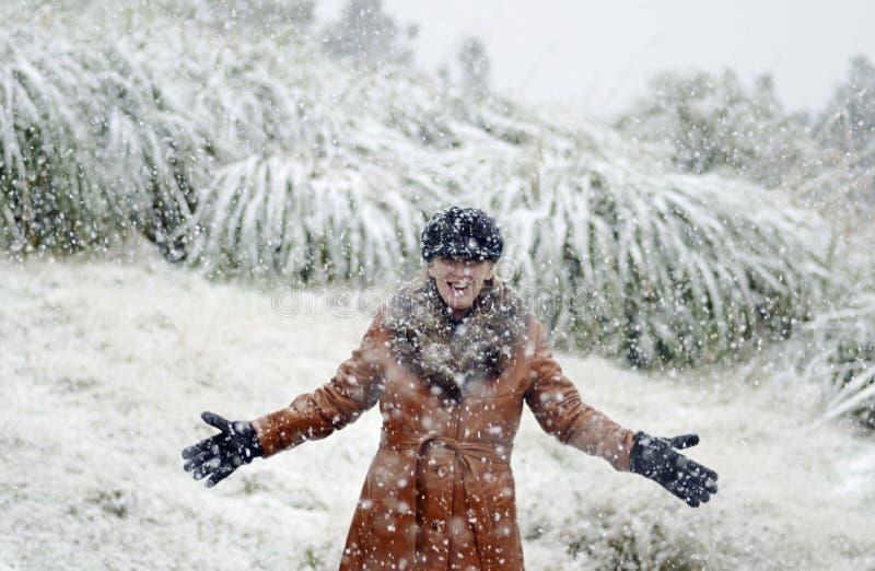 Glückliche Frau, die den fallenden Schnee genießt lizenzfreies stockfoto
