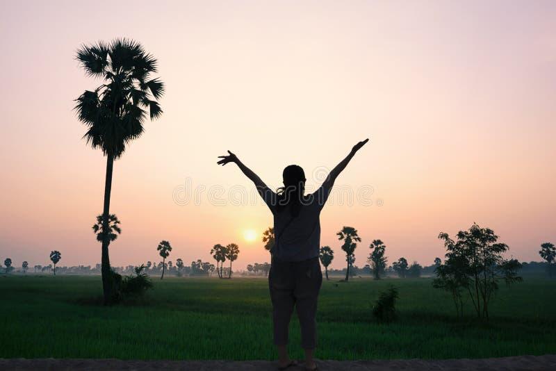 Glückliche Frau, die den Sonnenuntergang in der Natur schaut stockbild