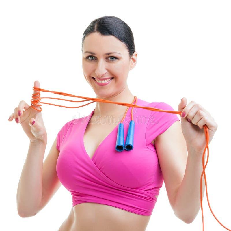 Glückliche Frau, die in der Turnhalle mit einem Seil ausarbeitet. stockfotografie