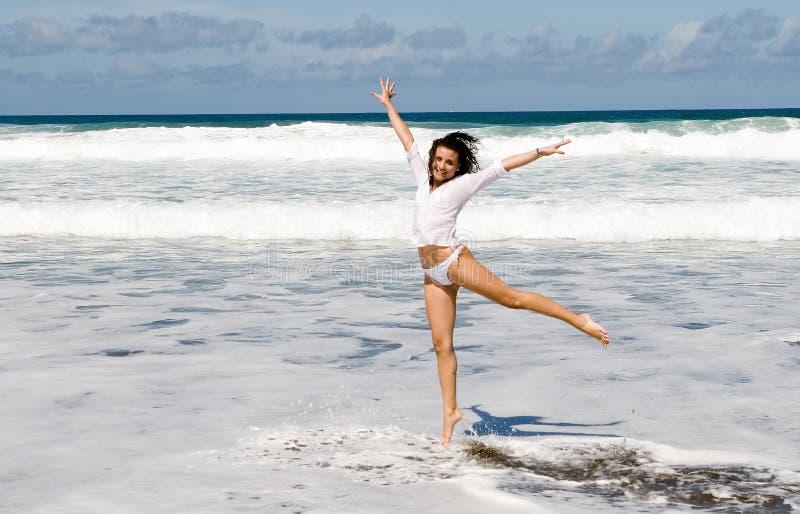 Glückliche Frau, die in die Küste springt lizenzfreies stockbild