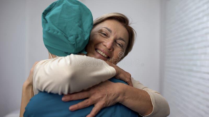 Glückliche Frau, die Doktor, gute Testergebnisse, Wiederaufnahme und Erlass, Dankbarkeit umarmt stockfoto