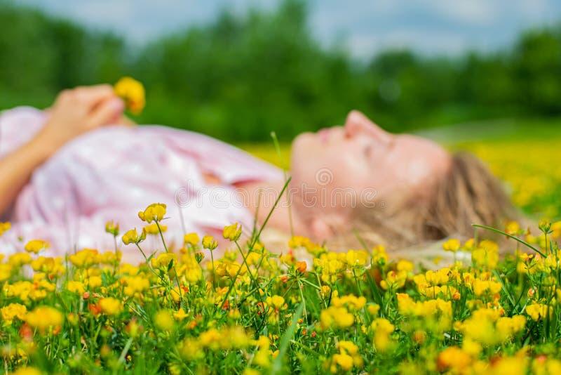 Glückliche Frau, die draußen auf dem Feld im Gras mit gelben Blumen liegt Genie?en Sie Natur Allergie geben frei stockbild
