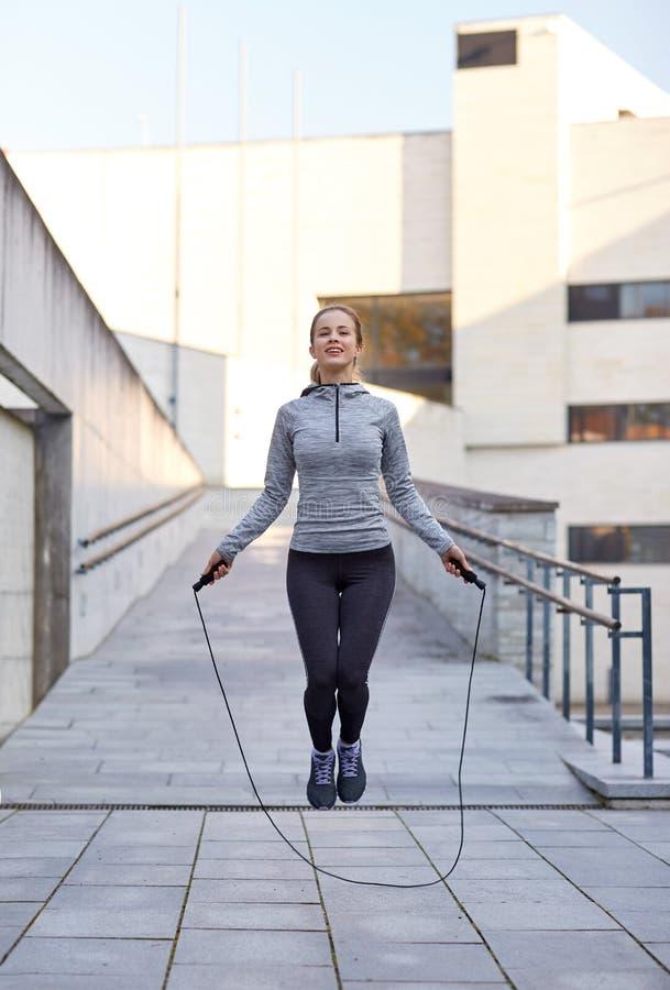 Glückliche Frau, die draußen mit Seilspringen trainiert stockbilder
