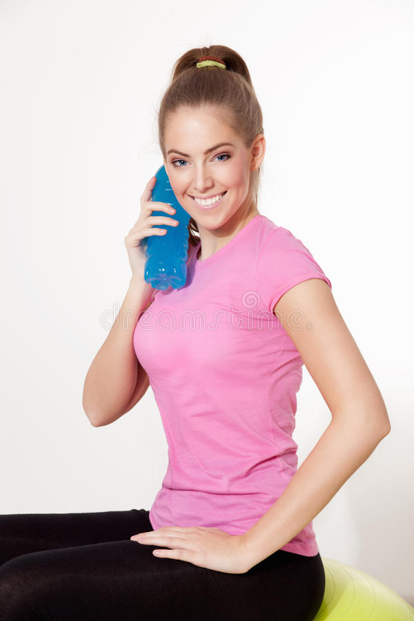 Glückliche Frau, die ein Getränk während des Trainings hält lizenzfreie stockfotos