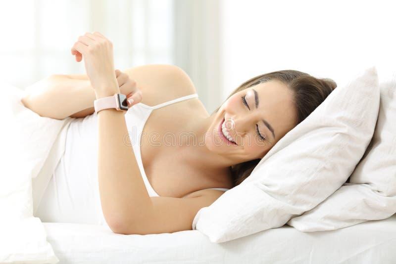 Glückliche Frau, die ein smartwatch auf dem Bett verwendet stockfotos