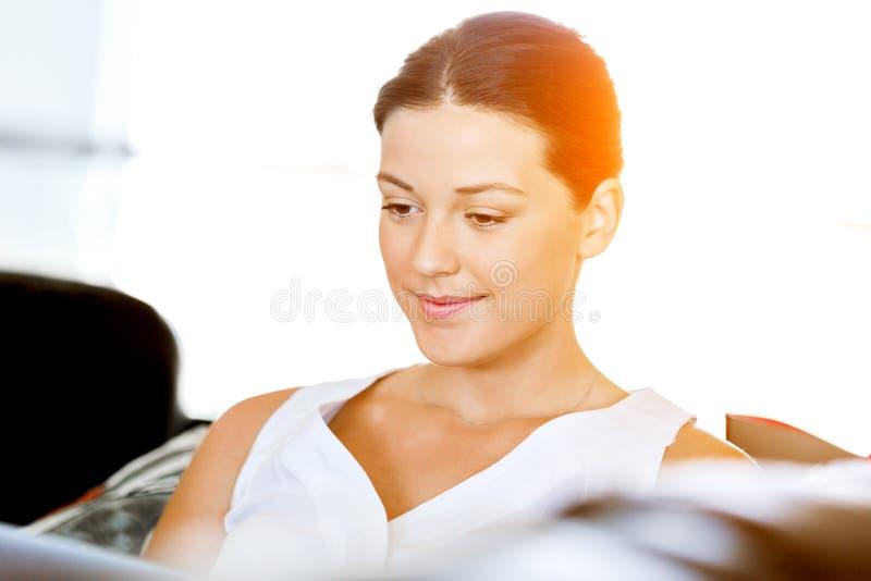 Glückliche Frau, die eine Zeitschrift sitzt auf einem Sofa liest stockfotos