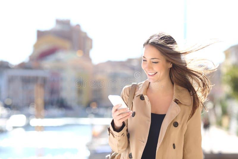 Glückliche Frau, die an einem intelligenten Telefon geht und schreibt stockfoto