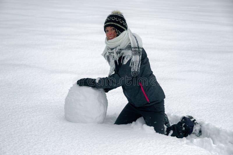 Glückliche Frau, die einen Schneemann maiking ist lizenzfreies stockbild