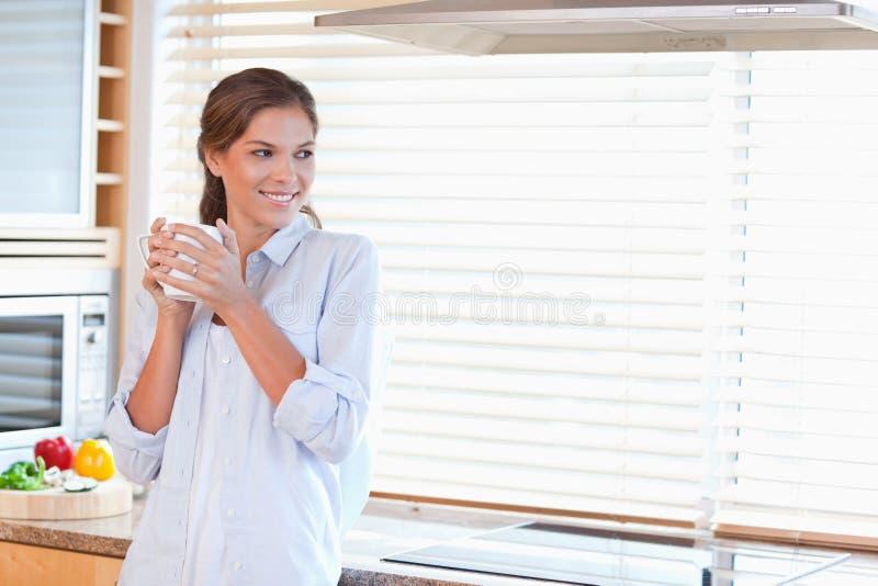 Glückliche Frau, die einen Tasse Kaffee hält lizenzfreie stockfotografie