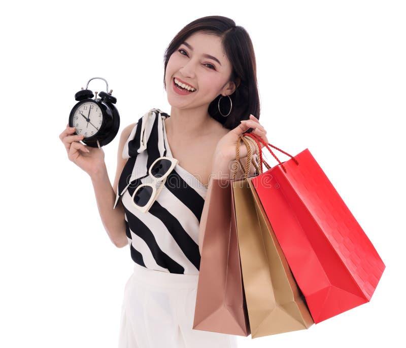 Glückliche Frau, die Einkaufstasche- und Uhrisolat auf Weißrückseite hält stockfotografie