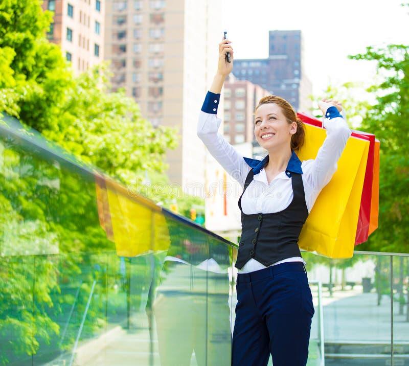 Glückliche Frau, die Einkaufstaschen hält und im Einkaufszentrum lächelt stockbilder