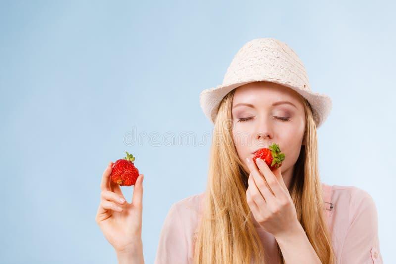 Glückliche Frau, die Erdbeeren hält stockbild